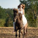 Frau mit weißem Hochzeitskleid auf Islandpferd im Galopp