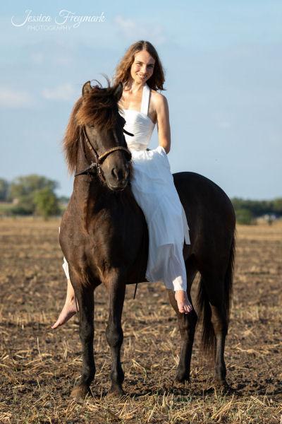 Frau mit weißem Hochzeitskleid auf Islandpferd