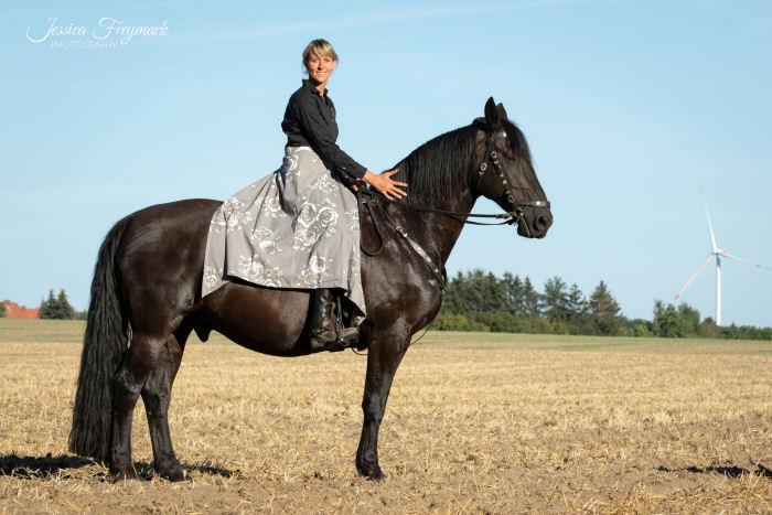Mit grauem Rock auf schwarzem Pferd