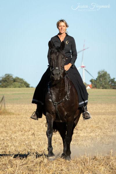 Schwarzes Kleid auf schwarzem Pferd