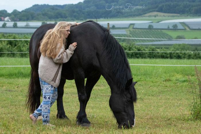 Mensch lehnt mit geschlossenen Augen am Pferd