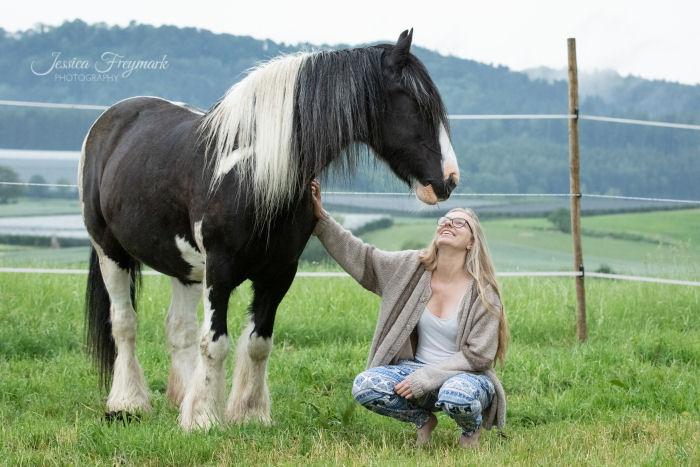 Frau hockt neben ihrem Pferd und schaut zu ihm auf